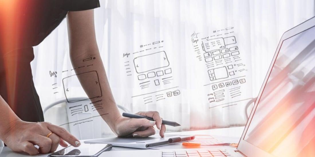 Persona realizado un diseño UX/UI en una notebook sobre escritorio