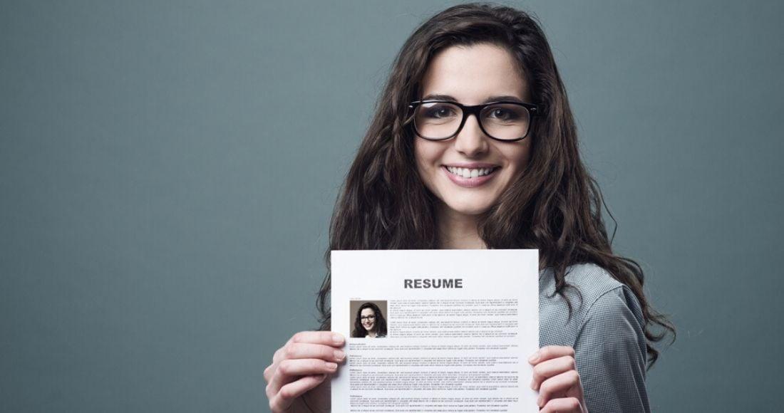 Joven sonriente exhibe su currículum vitae para hallar trabajo en tecnología mientras sonríe
