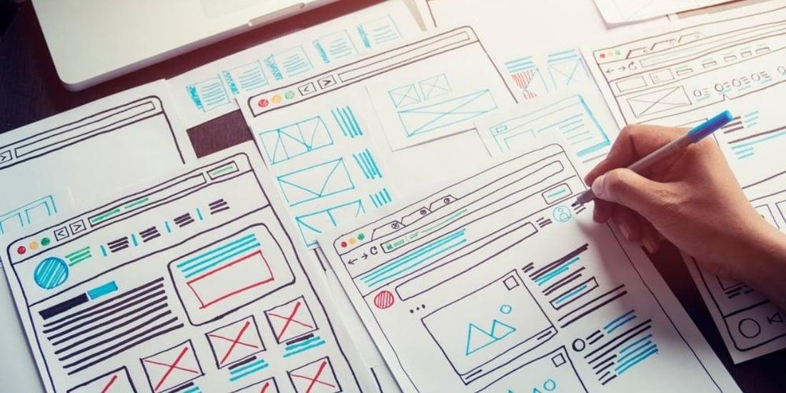 persona escribiendo sobre planos de Diseño UX UI sobre papel